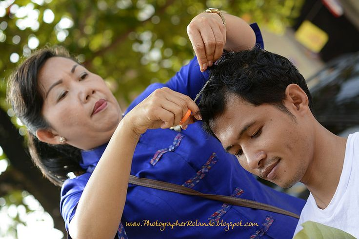 Family members participate in the ritual haircut from the candidate monk in Phon Phisai Nong Khai Thailand