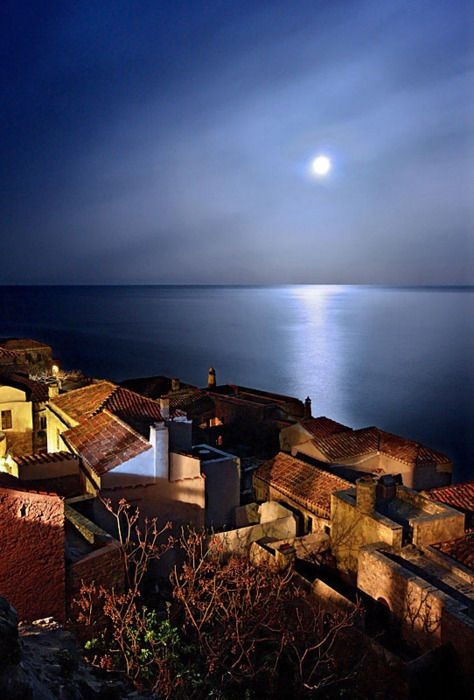 A full moon rises as night falls over Monemvasia, Greece