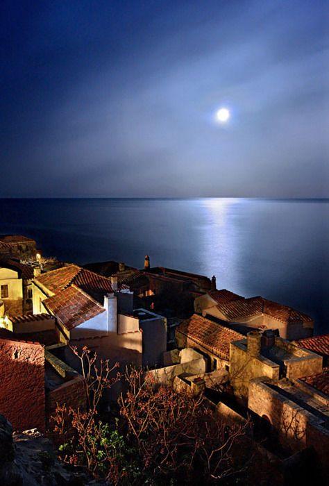 A full moon rises as night falls over Monemvasia, Greece
