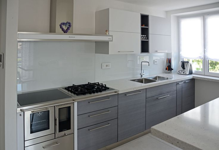 White and grey custom kitchen with steel stove: a bright environment where show off own creativity.