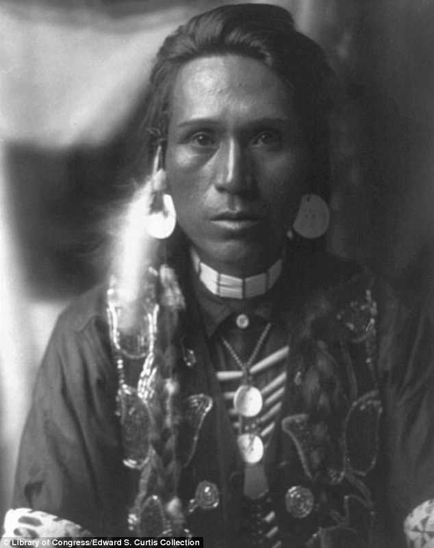 Focus: A young Yakima man stares straight into the camera wearing shell disk earrings, ca. 1910