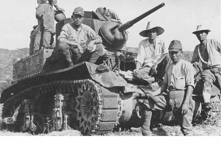 Philippines, early 1942. Japanese Soldiers posing with a captured American M3 Stuart Light Tank.