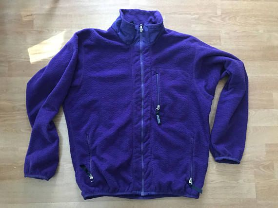 """Vintage purple Patagonia fleece jacket. Zippered front. Marked large, please see measurements below. Measures approximately Shoulder seam to shoulder seam 22"""" Armpit to armpit 24"""" Length 28"""" Sleeve length 24.5"""" Marked Patagonia, made in usa Vintage condition- some wear on"""
