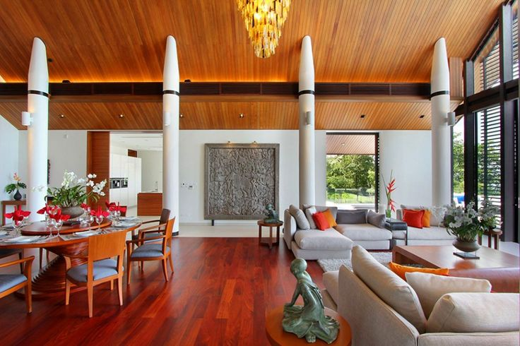 The Attractive Villa in Thailand with the Amazing Landscape of Phuket Foothills: Luxury Interior Design For Villa With Laminated Wooden Floor And Ceiling And Simple Cahir And Round Table With Gray Sofa And Orange Pillows And Antique Sculpture And Chandelier And White Pole
