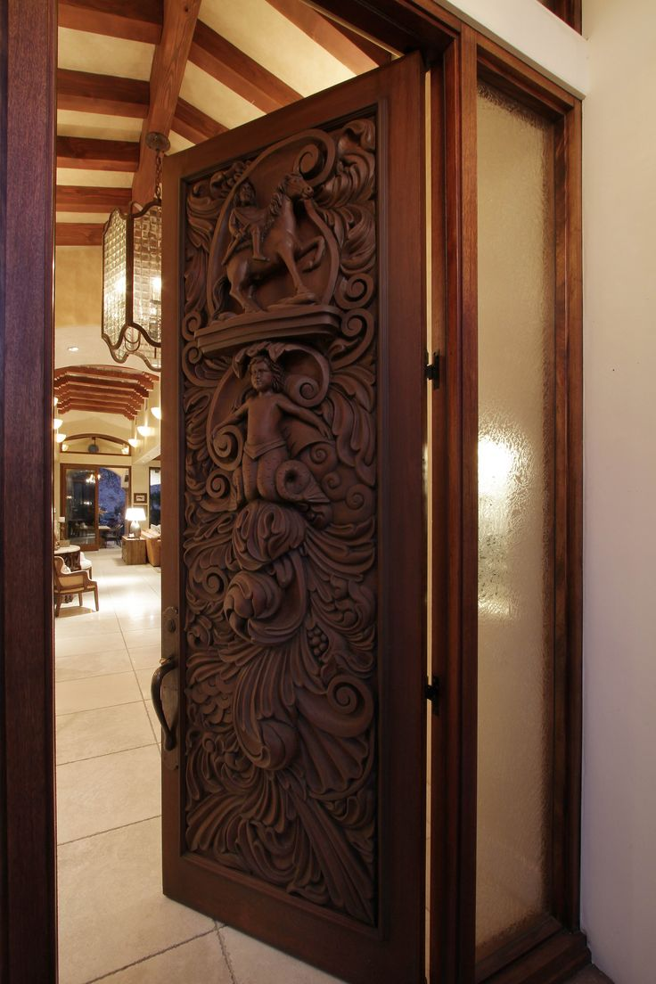 Beyond the ornate hand carved entry door lies a desert for Hand carved wood doors
