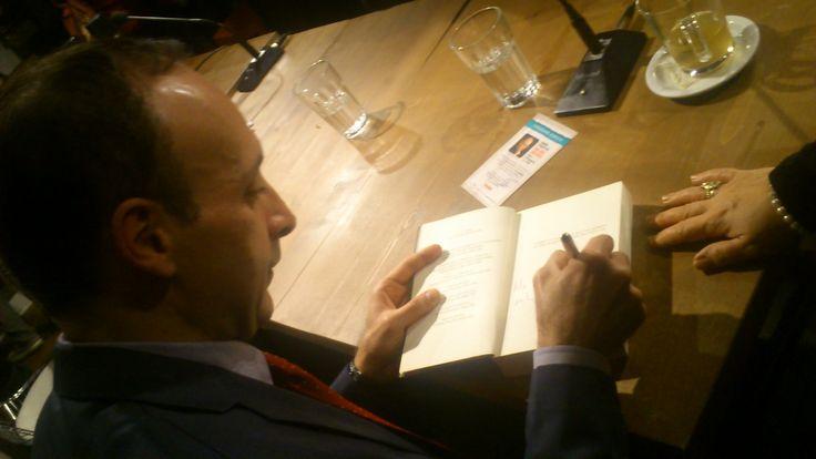"""Ο συγγραφέας Θάνος Κονδύλης υπογράφει με προσωπική αφιέρωση το νέο του βιβλίο, """"Μια ζωή, ένα φιλί"""". Το βιβλίο βασίζεται σε πραγματικά γεγονότα και πραγματεύεται το ευαίσθητο ζήτημα της ενδοοικογενειακής βίας."""
