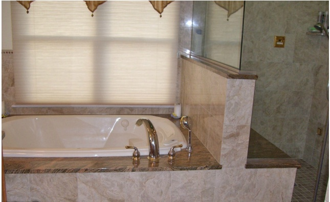 This bathtub and the surrounding marble tile is beautiful