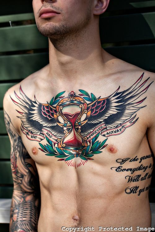 A tattooed young male displays a colourful chest piece tattoo on his muscular body. The white skin background shows off the wings and hour glass of the intricate tatt design to create  a photographic image of masculine beauty.