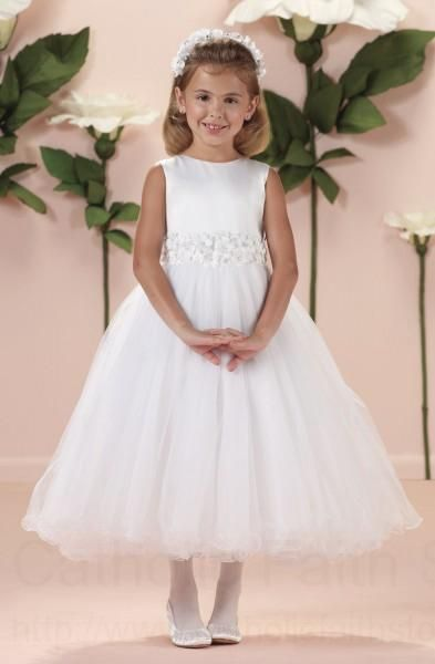 This First Communion dress proves that simple is stylish and sophisticated! The plain white sleeveless Satin bodice and contrasting princess style Tulle skirt are separated by a gorgeous waistline consisting of layer upon layer of Satin flowers with sequin, pearl and clear beaded centers. A stunning complement to this elegant dress!
