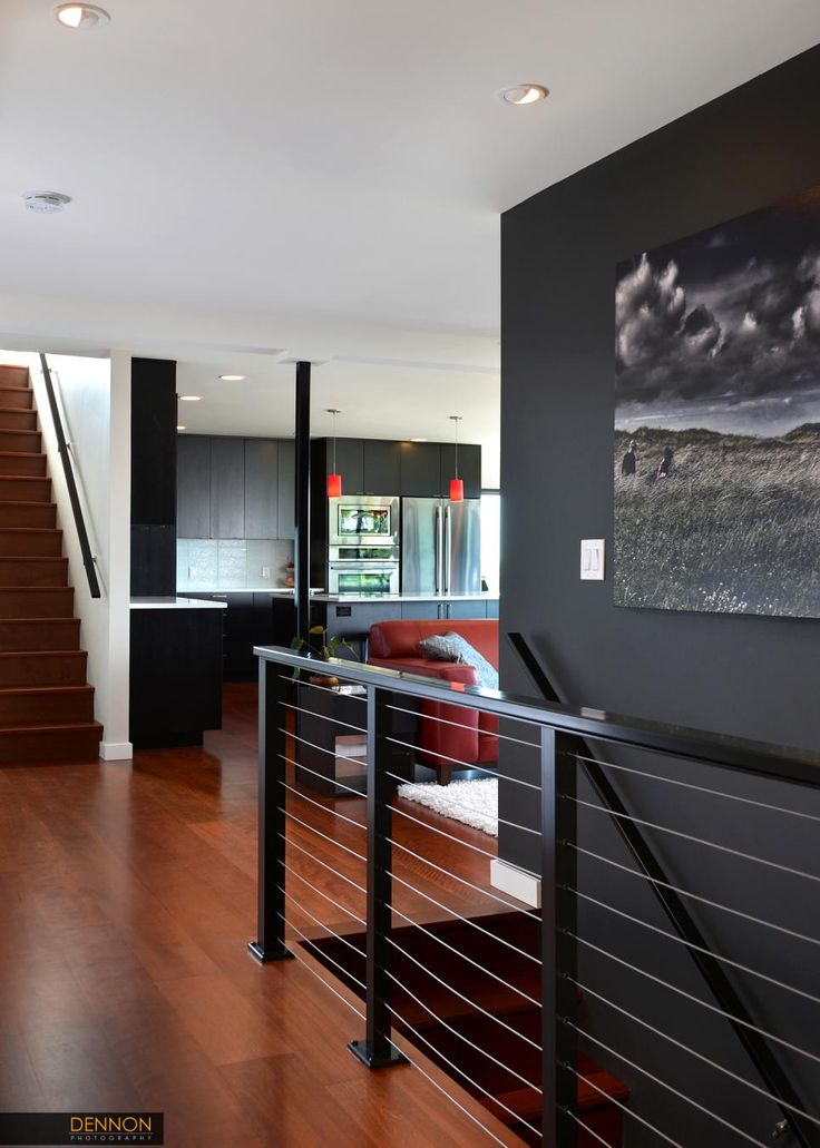 A combination of metal and cable creates a railing that borders the staircase in this contemporary living space. A black accent wall features a dark piece of artwork as you descend the stairs.