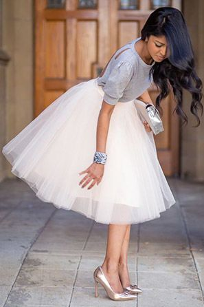 Bride wearing metallic heels, tulle skirt and comfortable sweater for her rehearsal dinner.
