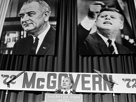 1972 ELECTION - With pictures of Lyndon Johnson, left, and John F. Kennedy, right, behind him, McGovern introduces Sargent Shriver as his running mate to the Democratic National Committee in August 1972.