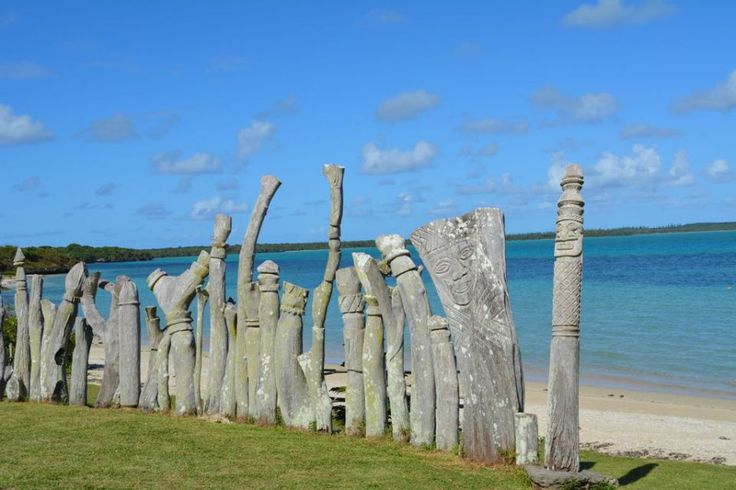 Totems watching over the statue Maurice Bay in the Isle of Pines