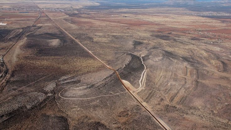 """Arial photo of the US-Mexico Wall in desert - """"This huge border, which is 3000 km long, has so many different micro habitats, and micro cosms, that each place is affected differently by the wall and each place has different animal and plant species, different soil system or different hydrology that's going to be affected. """""""