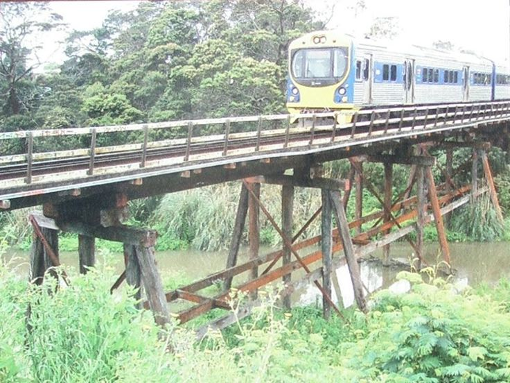 2007. Whau rail bridge before the wooden structure was replaced with concrete piers. Ontrac photo on Olympic Park signage.