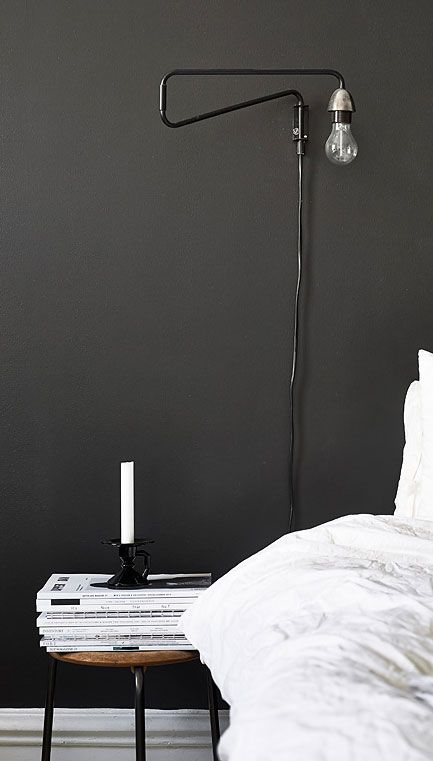 = black wall, mounted bedside lamp and white linen -- I'm thinking about black (or near-black) for our master bedroom.