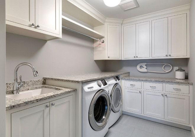 The L-shaped laundry room features white cabinets painted in Benjamin Moore OC-17 White Dove, gray ceramic tiles in a brick pattern and granite counters.Luxurious Cottage Interiors