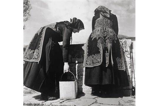 Nelly: Greek farm women in costume getting water at the well Greek farm women in costume getting