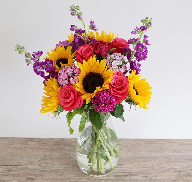 Vibrant Summer Bouquet: • 6 Sunflowers • 4 Cerise rose • 3 Purple stocks • 5 Sweet Williams