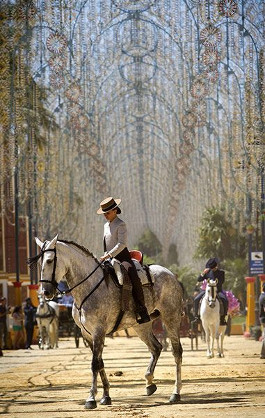 A woman rides a horse during a horse fair in Jerez