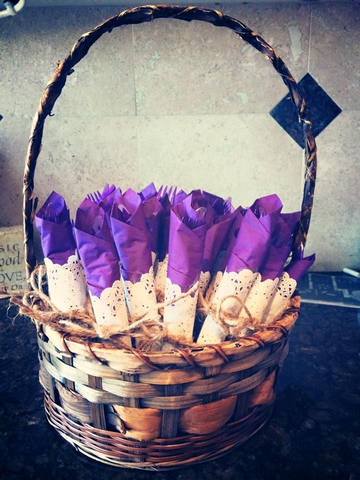 Bridal shower luncheon...basket of plastic ware, wrapped in purple napkins, doily and juut.
