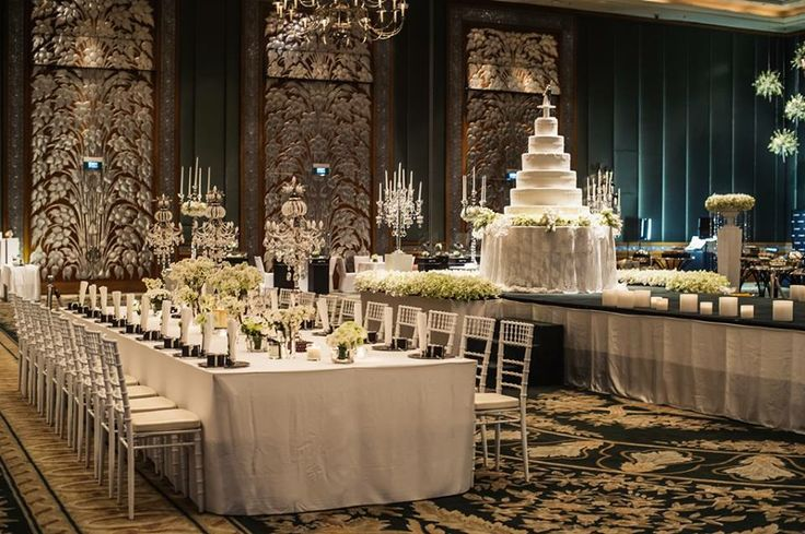 A dramatic white wedding reception with crystal candelabras, frosted glass and a sky-high cake tower in Grand Hyatt Erawan Bangkok's Grand Ballroom.