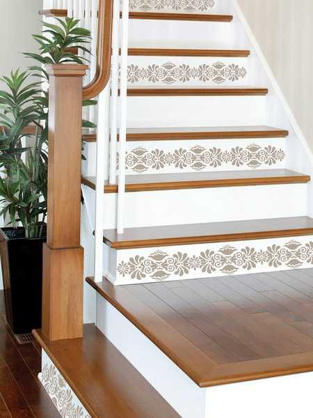 painting wood stairs wisers in white and applying stenciling decoration patterns on every second riser