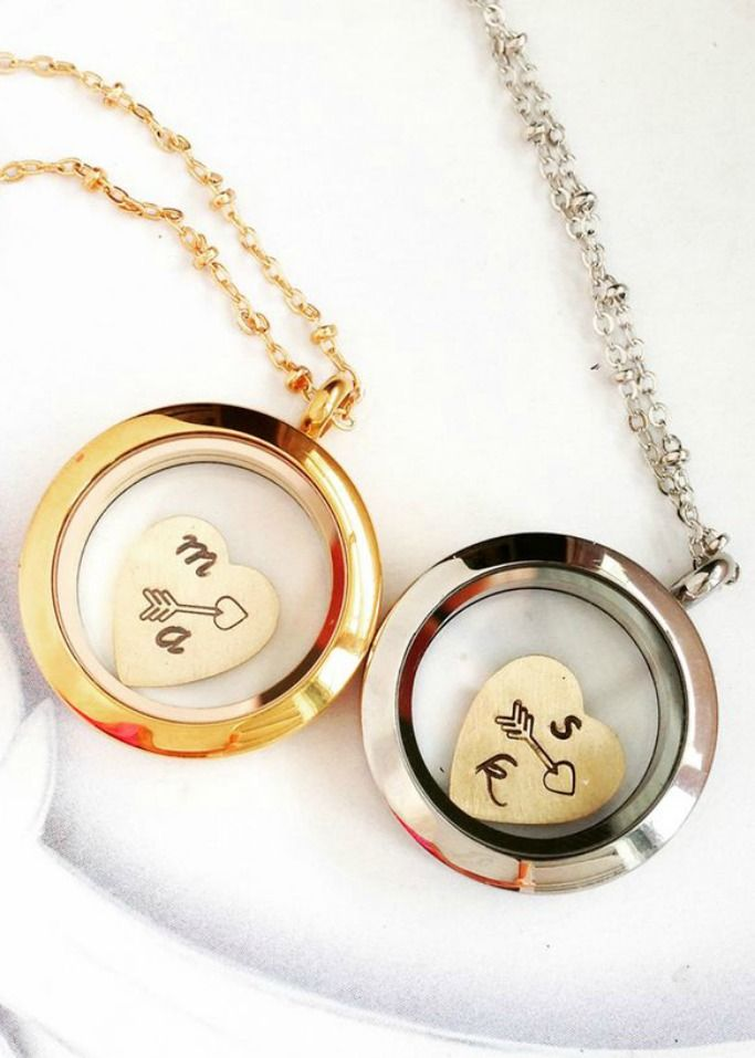 This locket holds a small charm stamped with two initials and an arrow. A small glass encasement holds the heart allowing it to float freely inside. LUV this <3