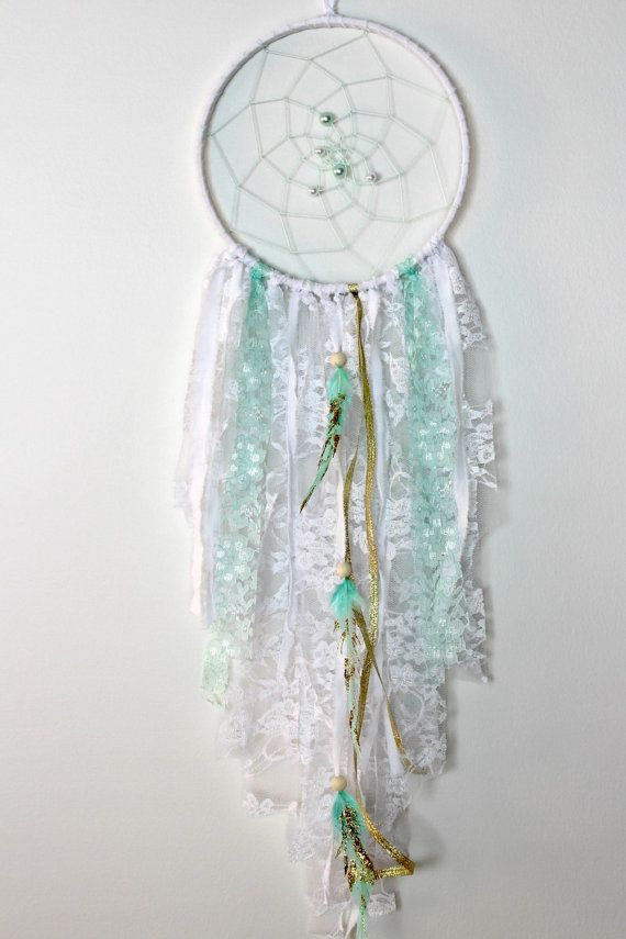 Mint, Gold and White Dream Catcher  Pictured dream catcher measures 8 across hoop by 29 in length including hanger  This boho chic dreamcatcher features a mint web in the center of the cotton wrapped hoop. The bottom has white, gold and mint lace, ribbon and cotton. For the finishing touch I added three mint feathers with gold glitter accents. Larger sizes will feature more pearls in the web.  Perfect for a nursery or any space in your home!  ~~Lace and beads may vary slightly depending on…
