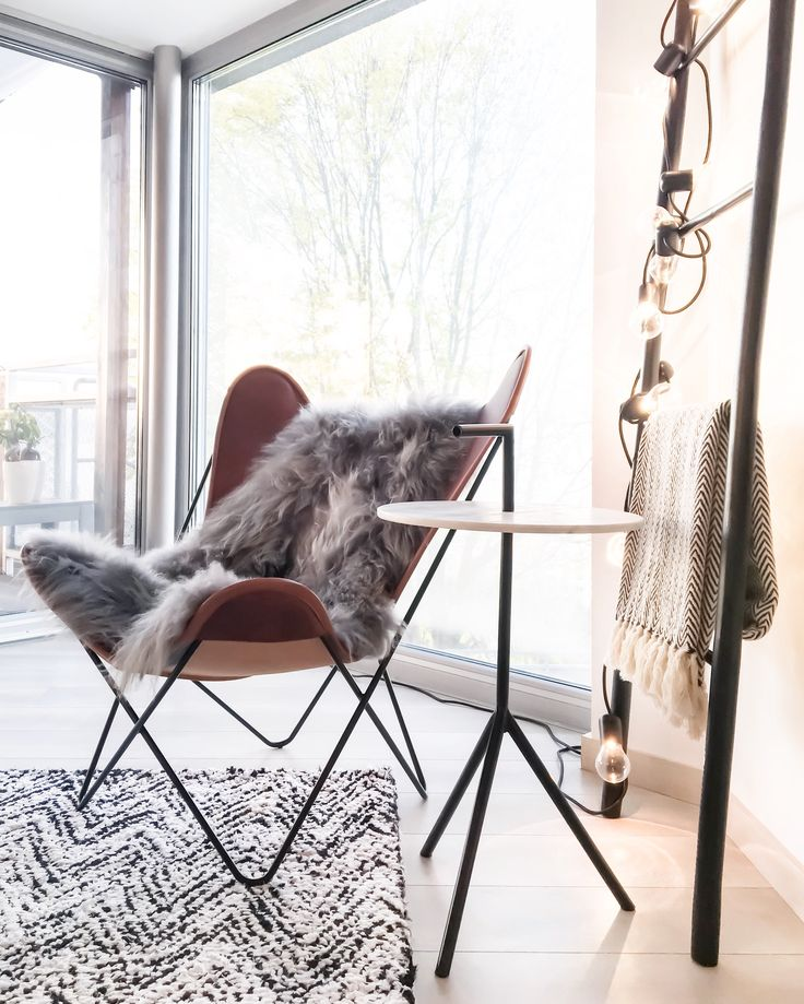 Butterfly chair, J-line marble tripod side table, Broste Cphg decorative ladder with Ikea chain ligh, Madam Stoltz rug.