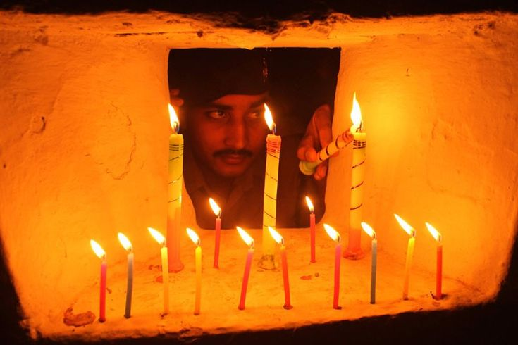 An Indian Border Security Force soldier lights candles inside a bunker at the India-Bangladesh border on the outskirts of Agartala