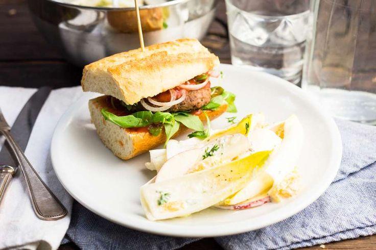 Recept voor hamburgers voor 4 personen. Met zout, boter, peper, hamburger, witlof, appel, stokbrood, mandarijn, mayonaise, yoghurt, ui, rucola en tomatenketchup
