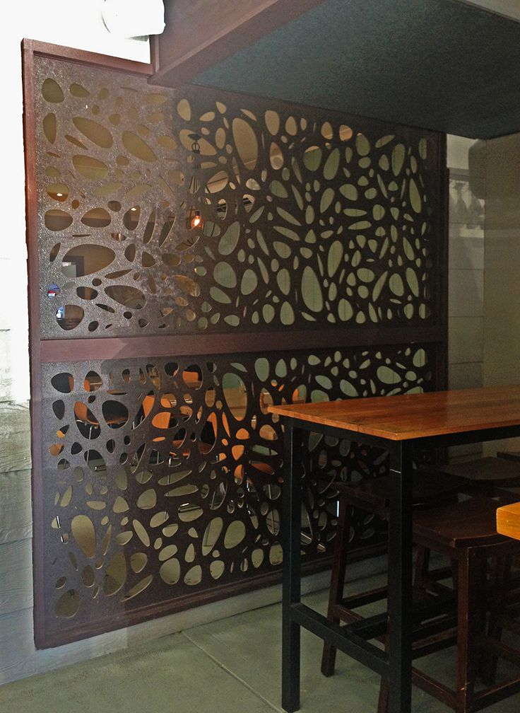 Laser cut decorative screens installed at The Fig & Olive Cafe, Phillip Island. These are QAQ's 'Cayman' design in compressed hardwood with a 'Jarrah' stain finish.