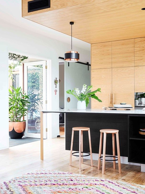 "Black accents and finishes care of chic ""Cliff' bar stools from Vincent 2 and a striking copper and black steel pendant from Angelucci 20th Century give this stunning kitchen its contemporary edge."