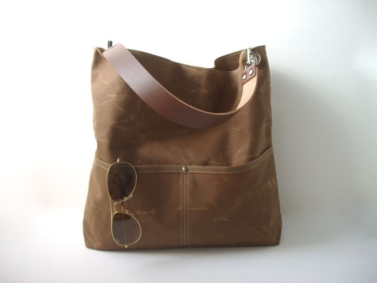 Our waxed canvas bucket bag is durable, lightweight and a breeze to carry. This rugged, natural canvas bag in Field Brown ages beautifully and looks better with a little wear and tear; becoming softer and more creased with use; giving it that sought after well-worn, lived in look. Our bucket tote has an easy-carry-shape and includes 5 slip pockets (2 outside and 3 inside) as well as a large interior zippered pocket. A double-wide, natural leather strap and nickel plated hardware complete the…