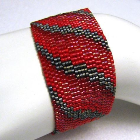 I had been toying with the idea of translating some traditional bargello patterns into peyote. The December/January 2008 Etsy BeadWeavers Challenge theme of Red presented the perfect opportunity. This cuff is based on a simple ribbon pattern for bargello needlework. I use Japanese delica beads in matte metallic grey and three different shades and finishes of red to create this piece with one-, two-, three-, and four-drop peyote stitches. This piece is 1.1 (28mm) wide and will be made to 7…