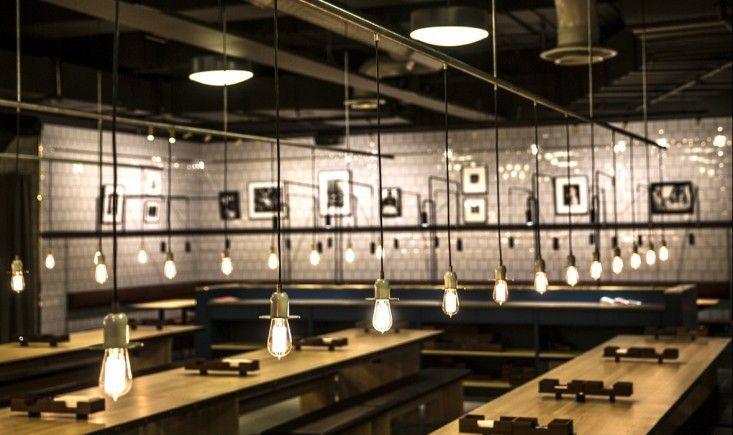 Printz Mathall, Stockholm, long wood communal tables, Run pendant lights, white ceramic tiles | Remodelista