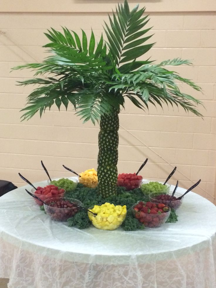 Pineapple palm tree fruit display 8-23-15.  I watched a video on how to make the base and it looked easy enough. That was until I went to the home improvement store and could not find the pvc piece and round board that was used in the video. My unconventional and last minute effort was buying a wooden paper towel holder with the pole that unscrews and screwing in a table leg that was for sale also. It worked perfect!!! I covered the pole and base in aluminum foil. I also used commodore palms…