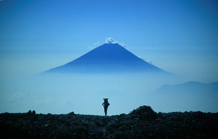 テントを担いで南アルプスを縦走する登山者、間ノ岳山頂部、遠景は富士山