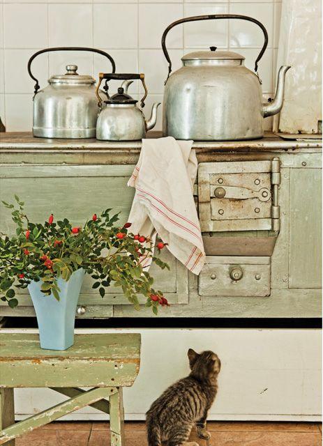 Cocina de una casa en la provincia argentina de Chubut con una antigua estufa económica, colección de pavas y piso de loza color marrón.