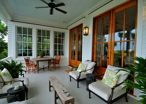 Love the windowed room abutting the porch, the beautiful french doors and the zones for conversation and eating.