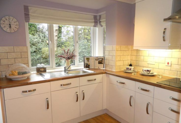 Interior designed very small kitchen, excellent use of white budget units, wood effect worktops and the combination of lavender walls and the brick tiles stop the whole thing turning into a pastiche.