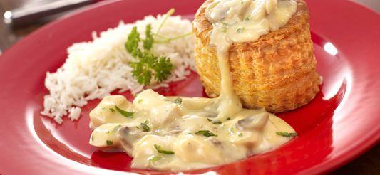 Verwarm de oven voor op th. 5 – 150° C om er de lege bladerdeeggebakjes in op te warmen.      Snij de kipfilets in blokjes en bak ze in een nootje boter (10 g) en de olie in een grote braadpan op een vrij hoog vuur. Snij ondertussen de champignons in plakjes.      Neem de bruingebakken kippenblokjes uit de pan en bak er de fijngesneden champignons in. Overgiet met 1 eetlepel citroensap en bak tot ze al hun vocht hebben vrijgegeven.      Smelt ondertussen de resterende boter in...