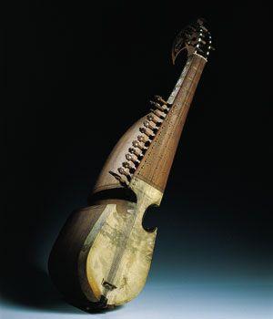 RABAB AFGANO  Llama la atención en este instrumento su enorme y apepinada caja excavada en una sola pieza de madera de morera, que incluye también el mástil. Asímismo son notables sus acentuadas escotaduras, inicialmente más propias en un instrumento de cuerda frotada que en uno de cuerda pulsada. El diapasón presenta decoraciones en marfil y cuerno tanto por la parte delantera como por el anverso, para protegerlo de la transpiración de las manos. La caja de resonancia está cubierta por una…