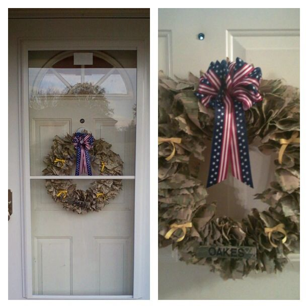 """Army camo wreath: straw wreath with wrapping still attached, cut 6in x 6in squares, yellow bows, flag ribbon bow, army name patch. Take the squares and gather all ashes together and hot glue onto wrapped wreath. Continue to glue all pieces close together to get the """"full"""" effect. Once pieces are glued and u r happy with the look, add your embellishments (yellow ribbons, flag bow and name patch.) attach a wire to back to hand"""