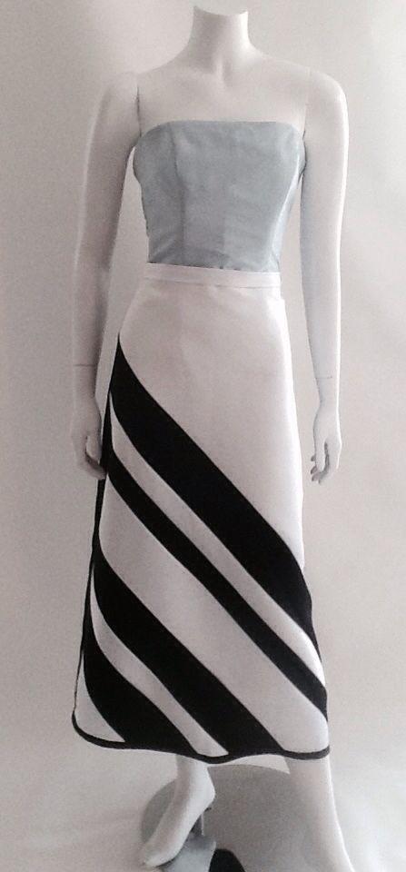 Cuerpo en tafeta de seda gris, falda mido en raso parte frontal bicolor en blanco y negro al beis, parte trasera en raso color negro.