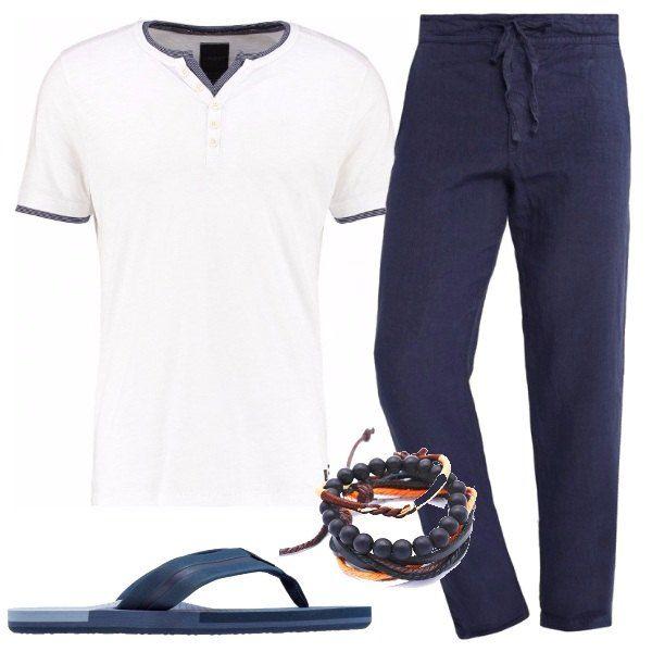 Pantaloni di lino blu, con vestibilità morbida e coulisse in vita. T-shirt bianca, con collo con bottoncini e finiture alle estremità blu. Infradito blu e set di bracciali di pelle, pietre e tessuto blu e arancione.