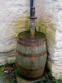 Rainwater harvesting  Rustic rain barrel. love the old pump.