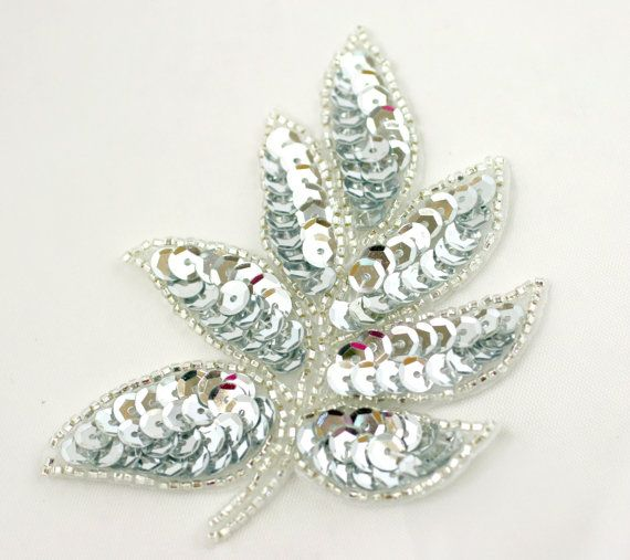 Sparkling silver sequins and silver beading make up this shiny leaf-shaped applique.  Perfect for wedding/event projects, DIY, paper craft, head pieces, sashes, cake decor...  Available in several colors!