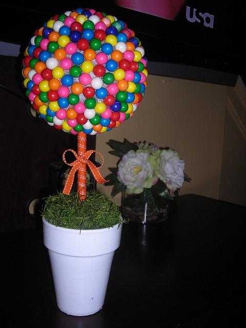 it is made using gumballs hot glued to a foam ball which i then insterted into the ceramic pot using a wooden dowel and more foam in the base of the pot.